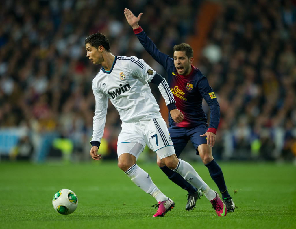 Cristiano Ronaldo (L) of Real Madrid controls the ball besides Jordi Alba of Barcelona appealing for a hands ball during the Copa del Rey semi final first leg match between Real Madrid CF and FC Barcelona at the Estadio Santiago Bernabeu on January 30, 2013 in Madrid, Spain.